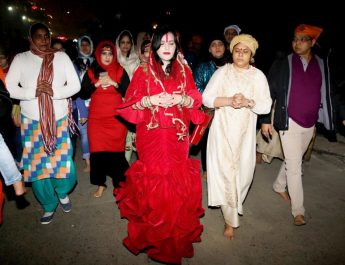 Radhe Maa in a red mermaid outfit - replete with a red purse and surrounded by devotees