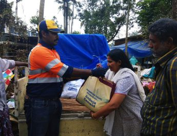 A woman receives Ambuja Cements flood relief material